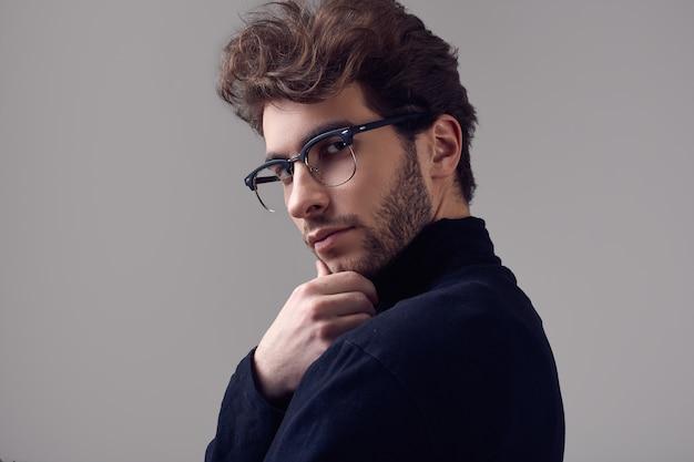 Uomo elegante bello con capelli ricci che indossa dolcevita e vetri neri