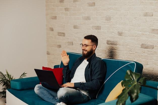 Uomo felice emotivo bello con barba e occhiali seduto sul divano blu e utilizzando il computer portatile per la comunicazione