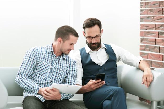 Dipendente bello con touchpad che spiega i dati al suo collega