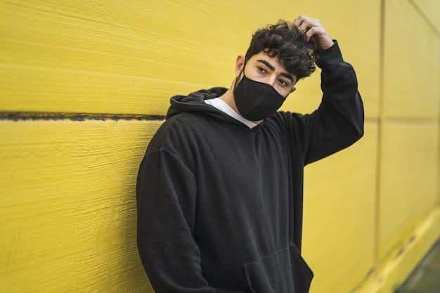 Bello pattinatore europeo in felpa con cappuccio in posa davanti a un muro giallo in un viso - nuovo concetto normale