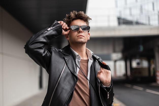 Bello giovane hipster europeo con acconciatura alla moda in giacca di pelle nera alla moda raddrizza occhiali da sole eleganti in una giornata di sole primaverile. bel ragazzo in abiti vintage in stile retrò all'aperto.