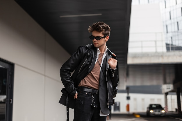 Bel giovane europeo in abiti oversize di moda giovanile con un'acconciatura alla moda sta riposando vicino a un edificio moderno in città in una giornata primaverile. pantaloni a vita bassa del ragazzo moderno in occhiali da sole alla moda all'aperto.
