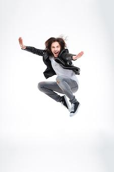 Bel giovane eccitato che salta e urla su sfondo bianco