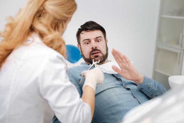 Bel giovane espressivo che sembra spaventato e riluttante ad avere i denti fuori mentre si paga una visita dal suo medico
