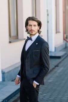 Bello modello di uomo d'affari di moda vestito con un abito elegante e in posa sulla strada. metrosessuale