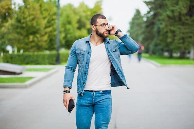 Uomo adatto alla moda bello che parla sopra il telefono sulla strada. indossare jeans denim casual.