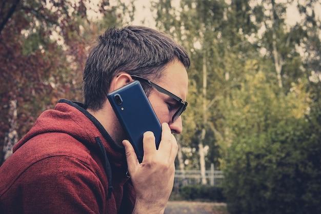 Bello hipster alla moda in occhiali da sole parlando al telefono sullo sfondo del parco autunnale. il giovane fa una chiamata su un telefono cellulare.