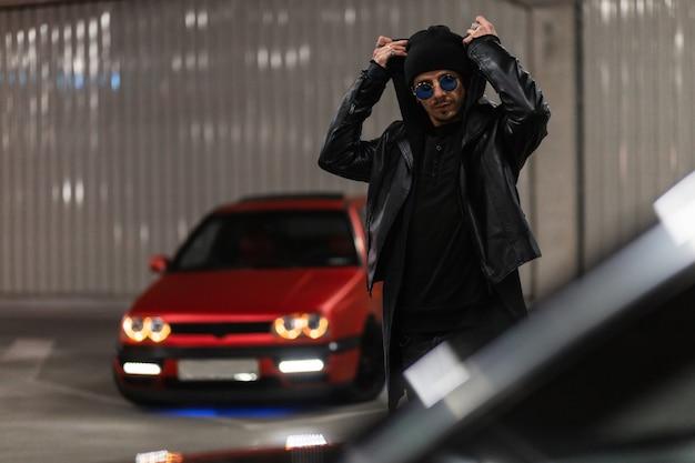 Bell'uomo alla moda che indossa occhiali da sole alla moda e un cappello nero con una giacca di pelle e una felpa con cappuccio indossa un cappuccio e cammina per strada di notte