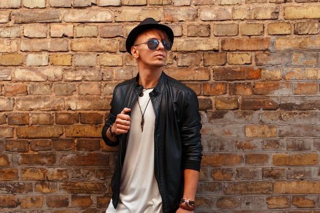Uomo alla moda bello con occhiali da sole in un cappello alla moda in una giacca di pelle nera vicino a un muro di mattoni