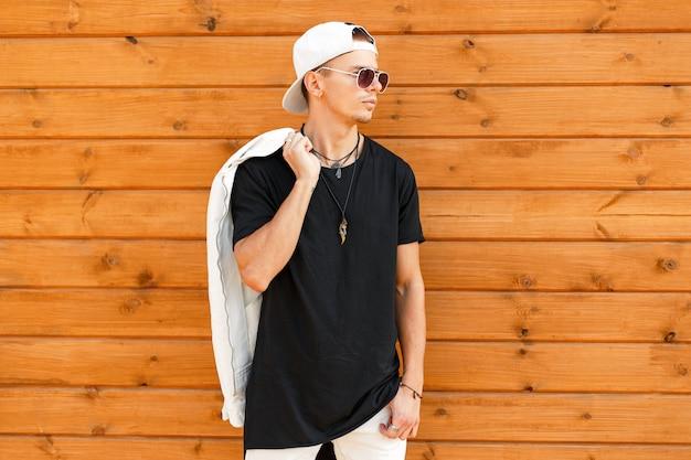 Bell'uomo alla moda con occhiali da sole in un berretto da baseball bianco con una maglietta nera e una giacca bianca vicino a una parete di legno