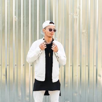 Bell'uomo alla moda con occhiali da sole in una giacca bianca con un berretto da baseball vicino al muro di metallo