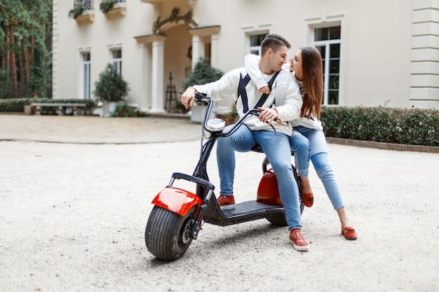 Uomo alla moda bello e giovane bella donna in abiti casual alla moda su una bici elettrica