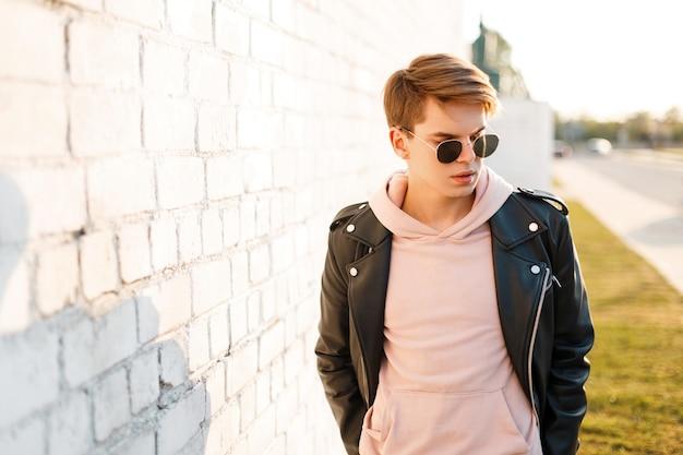 Uomo alla moda giovane hipster bello in occhiali da sole neri in elegante giacca di pelle nera in una felpa rosa in piedi vicino a un muro di mattoni bianchi dei raggi del sole. ragazzo attraente.