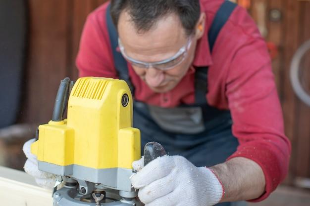 Bello concentrato sui processi di artigiano sul pezzo in legno con utensile di fresatura da vicino al laboratorio di cottage