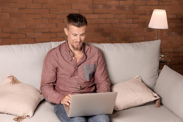 Libero professionista bello che lavora al computer portatile a casa