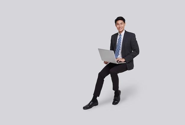 Sorriso dell'uomo d'affari asiatico del viso bello e amichevole in abito formale suo computer portatile con il computer portatile su sfondo bianco girato in studio.