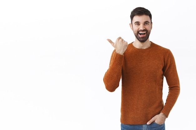 Bell'uomo barbuto sorridente dall'aspetto amichevole che invita a dare un'occhiata, indicando il pollice a sinistra e parlando, consigliare il prodotto, dare consigli su dove trovare l'oggetto in cerca, muro bianco