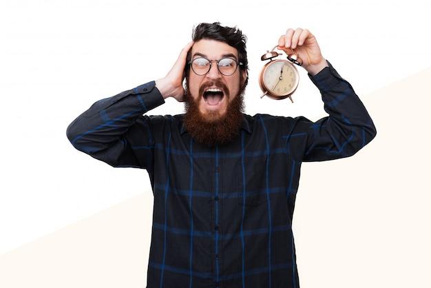 Bel ragazzo barbuto frustrato, tiene in mano un orologio vintage e preoccupato per il suo regime