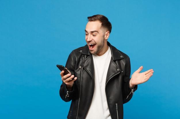 Bello divertimento felicissimo eccitato giovane uomo con la barba lunga in giacca di pelle nera t-shirt bianca utilizzando il telefono cellulare isolato sul ritratto in studio di sfondo muro blu. concetto di stile di vita delle persone mock up copy space