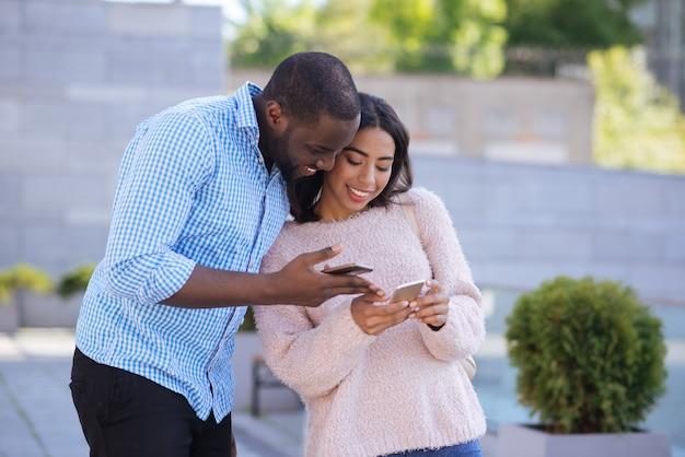 Bel ragazzo galante alla mano che incontra una bella ragazza e le chiede un numero mentre le da il suo