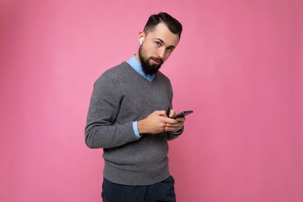 Bel giovane brunet barbuto di bell'aspetto che indossa un maglione grigio e una camicia blu isolata sul rosa