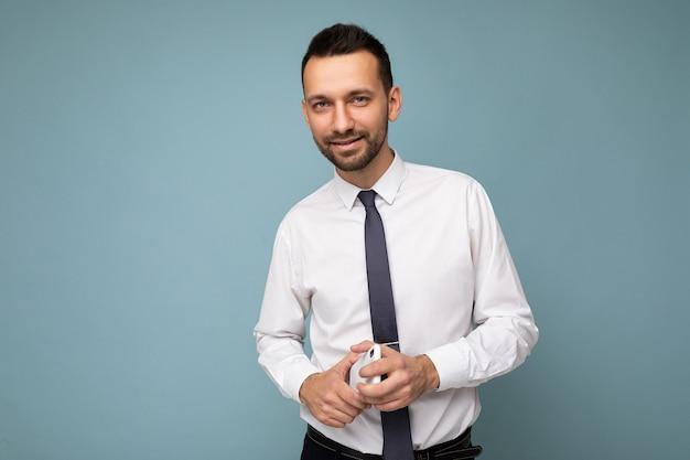 Bello bell'uomo brunet con la barba lunga con barba che indossa una camicia bianca casual