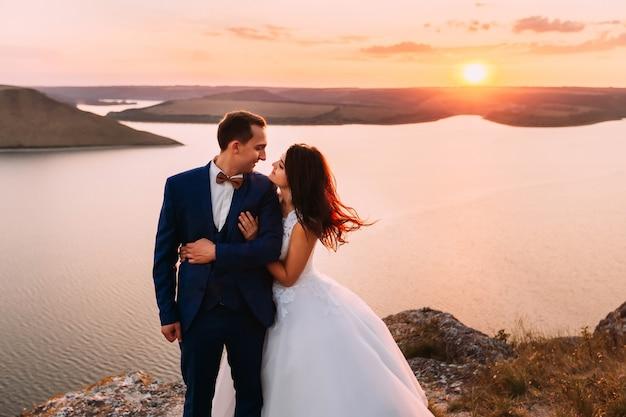 Sposo bello che esamina sposa splendida con capelli scuri lunghi