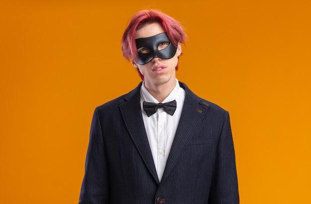 Bello sposo in completo con papillon e maschera mascherata con faccia seria in piedi sul muro arancione