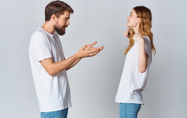 Bel ragazzo spiega qualcosa a una giovane donna su uno sfondo chiaro vista ritagliata famiglia copy space.