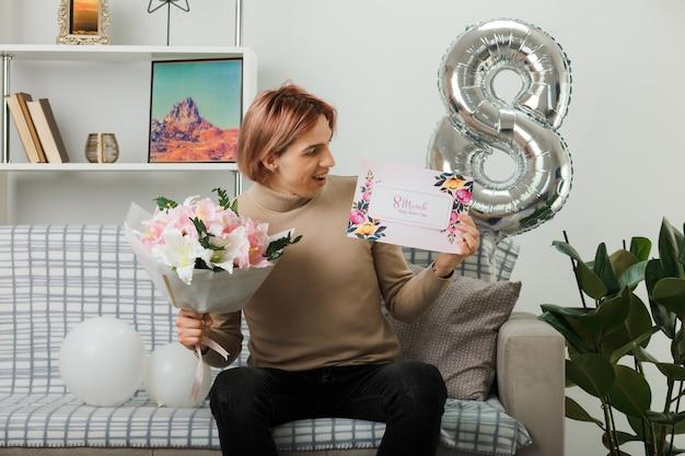 Bel ragazzo in una felice giornata delle donne con in mano un bouquet guardando la cartolina in mano seduto sul divano nel soggiorno