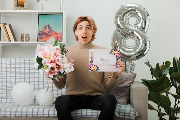 Bel ragazzo in una felice giornata delle donne che tiene un bouquet con una cartolina seduto sul divano in soggiorno