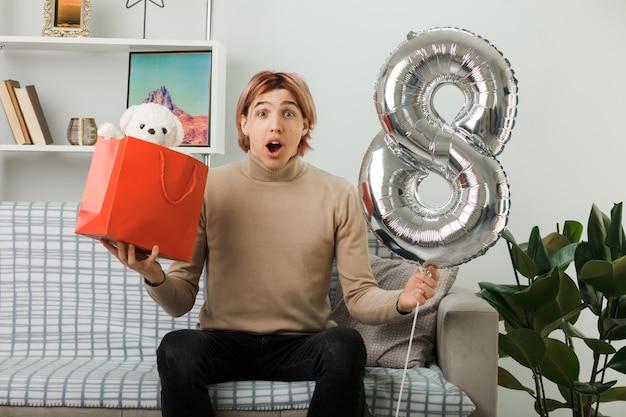 Bel ragazzo in una felice giornata delle donne che tiene il palloncino numero otto con un sacchetto regalo seduto sul divano in soggiorno