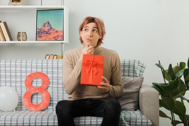 Bel ragazzo in una felice giornata delle donne con un regalo seduto sul divano in soggiorno