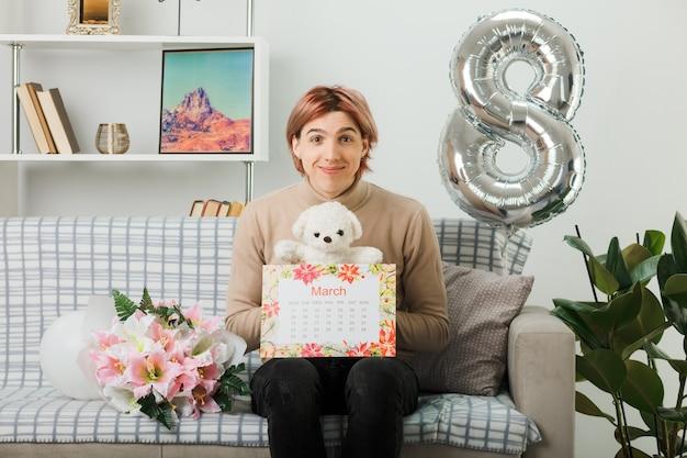 Bel ragazzo in una felice giornata delle donne che tiene orsacchiotto con calendario seduto sul divano in soggiorno