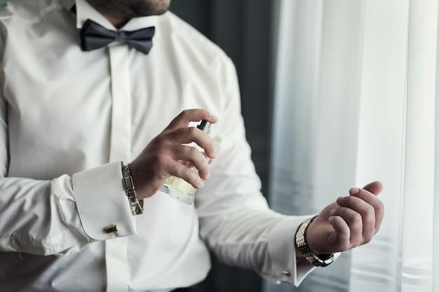 Bel ragazzo sta scegliendo i profumi, uomo elegante in abito con colonia, lo sposo si prepara al mattino prima della cerimonia di nozze