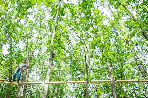 Bel ragazzo in un parco sulle corde raggiunge all'aperto