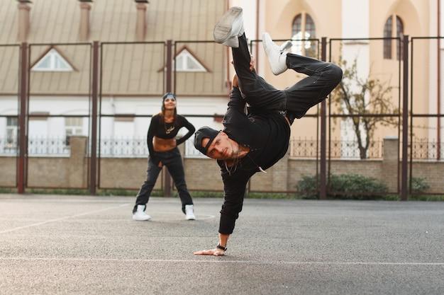 Bel ragazzo in abiti neri alla moda che ballano hiphop