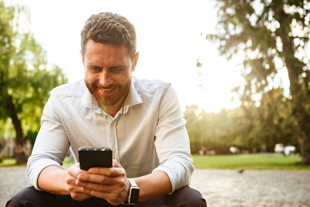 Bel ragazzo in camicia bianca, seduto nel parco e guardando il telefono cellulare nero che tiene nelle mani