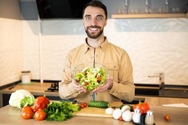 Bel ragazzo con barba e bel sorriso sta mostrando la sua preferenza uno stile di vita sano e sta mangiando cibo fresco.