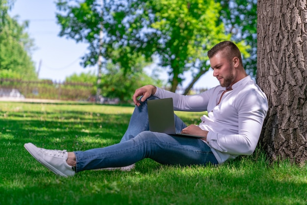 Un bel ragazzo con i capelli biondi e la barba corta si siede sull'erba vicino a un albero in un parco di campagna con un laptop aperto sulle ginocchia