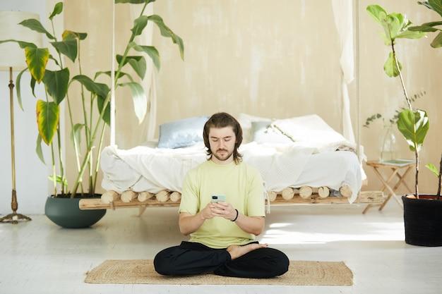 Bel ragazzo con capelli lunghi utilizzando il telefono seduto sul pavimento, insegnante di yoga che digita sullo smartphone a casa sul materassino yoga