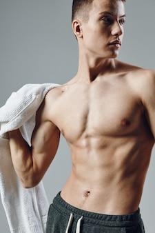 Bel ragazzo con asciugamani corpo muscoloso in mano colpo d'occhio laterale allenamento.