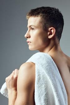 Bel ragazzo con un asciugamano sulla schiena su sfondo grigio vista posteriore.