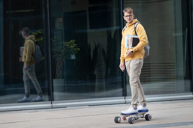 Bel ragazzo, giovane uomo, hipster, studente o allievo in bicchieri sul suo viso cavalcando skateboard elettrico urbano moderno con zaino, libri e libri di testo. trasporto ecologico, concetto di tecnologia.