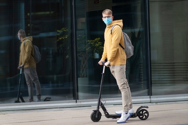 Bel ragazzo, giovane uomo in maschera medica sterile protettiva e occhiali sul suo viso cavalcando scooter elettrico urbano moderno con zaino. coronavirus, virus, epidemia covid-19, concetto di trasporto eco.