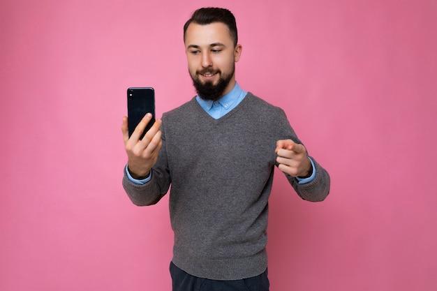 Uomo con la barba lunga del giovane brunetta fresco felice bello con la barba che indossa un maglione grigio alla moda e blu
