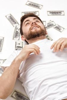 Bell'uomo felice con la barba in una camicia bianca sdraiata su centinaia