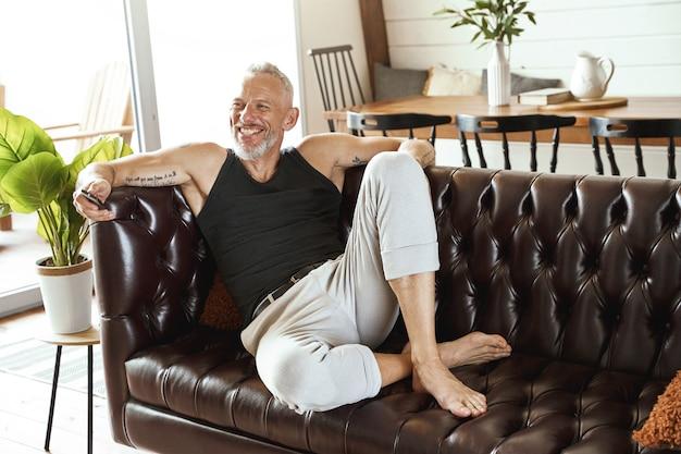 Un bell'uomo di mezza età felice in abiti casual con lo smartphone in mano che si rilassa comodamente