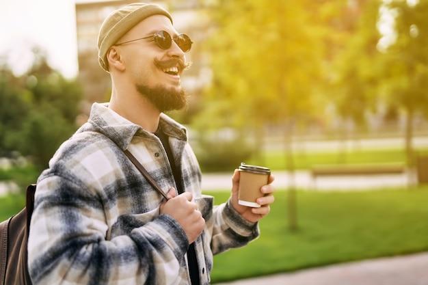 L'uomo barbuto sorridente felice bello beve il caffè fuori della via mentre cammina nel parco della città