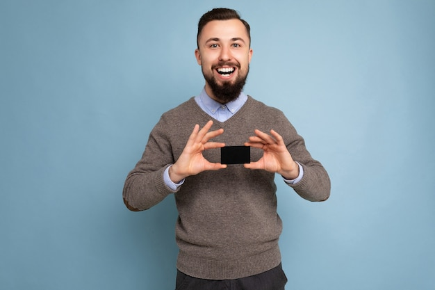 Bello sorridente felice bruna barbuto persona di sesso maschile che indossa un maglione grigio e una camicia blu isolata sulla parete di fondo tenendo la carta di credito guardando la fotocamera